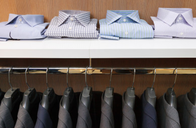 Row of men suit jackets on hangers and shelf with shirt in clothing store